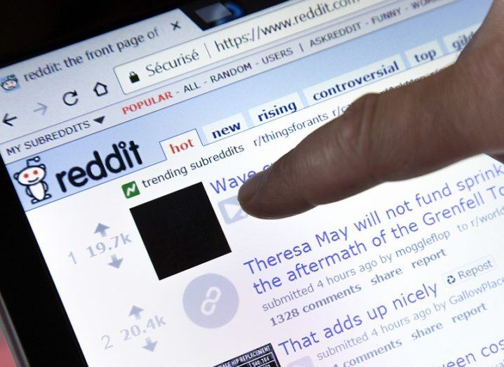 Person pointing their finger at the Reddit homepage on a laptop screen.