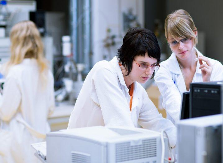 Two women researchers in white lab coats analysing data on a computer screen.