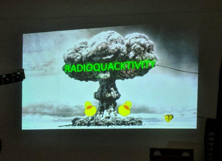 A projection on a white board displays a mushroom cloud and two yellow rubber ducks along with the title 'Radioquacktivity'.