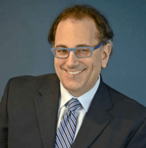 Dr Jules Polonetsky smiling, wearing a black suit with a blue tie and white shirt.