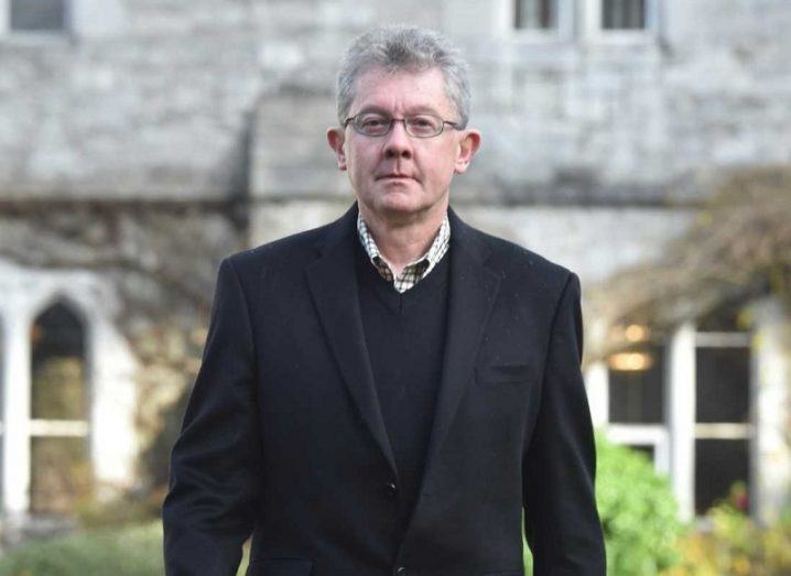 Grey-haired man with glasses in a black suit jacket and jumper standing on the campus of UCC.