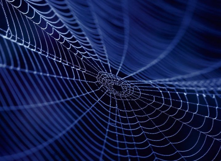 A close-up image of a spider web at night time.