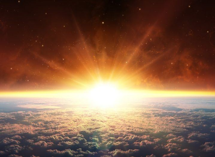 A bright sun rising over the far side of Earth as seen from above our planet.