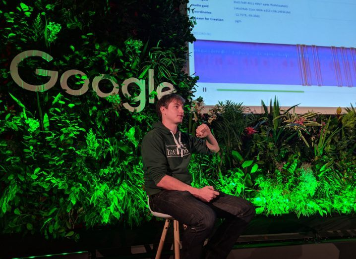 Young man in an Ireland rugby hoodie on stage at a Google event surrounded by foliage under a large screen.