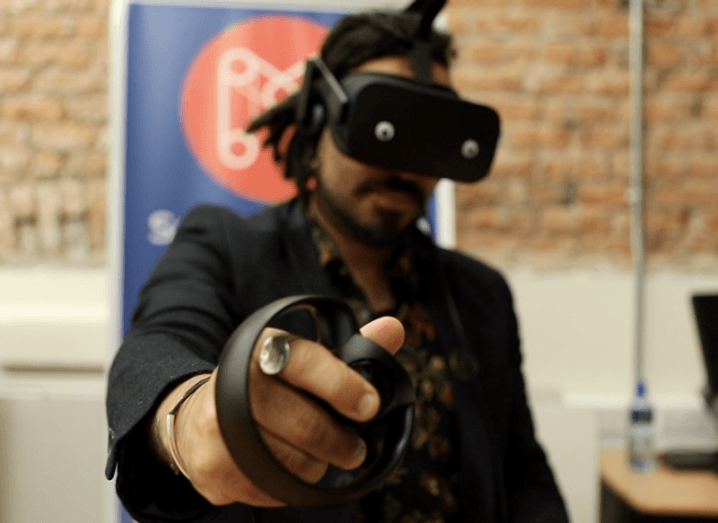 Close-up of a man using Oculus VR headset and hand control device with a blue banner and brick wall in the background.