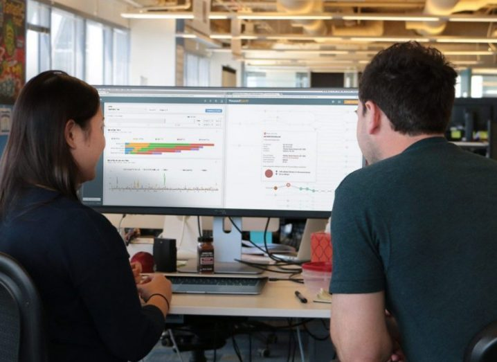 Two IT staff using the ThousandEyes network intelligence platform.