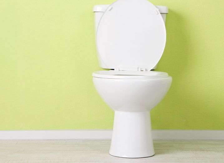 White toilet with open lid against a bright green wall.