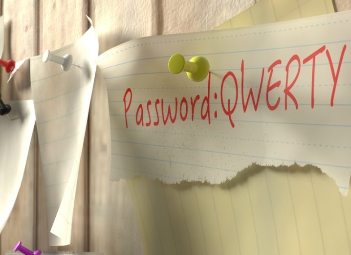 A piece of paper with a password written on it, pinned to a wall. Poor cybersecurity concept.