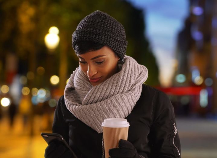 A woman using her smartphone on a city street in the evening. She is holding a cup of coffee and wearing winter clothes.