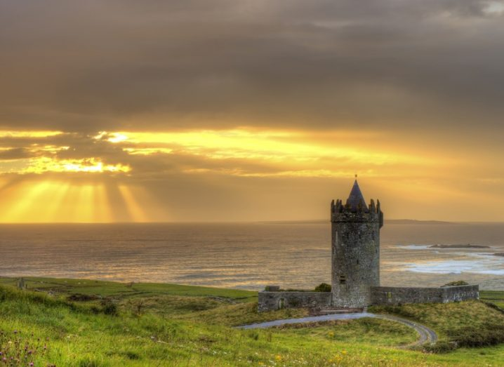 Doonagore Castle, located near the coastal town of Doolin in Co Clare. The sun shines on the sea in the background.