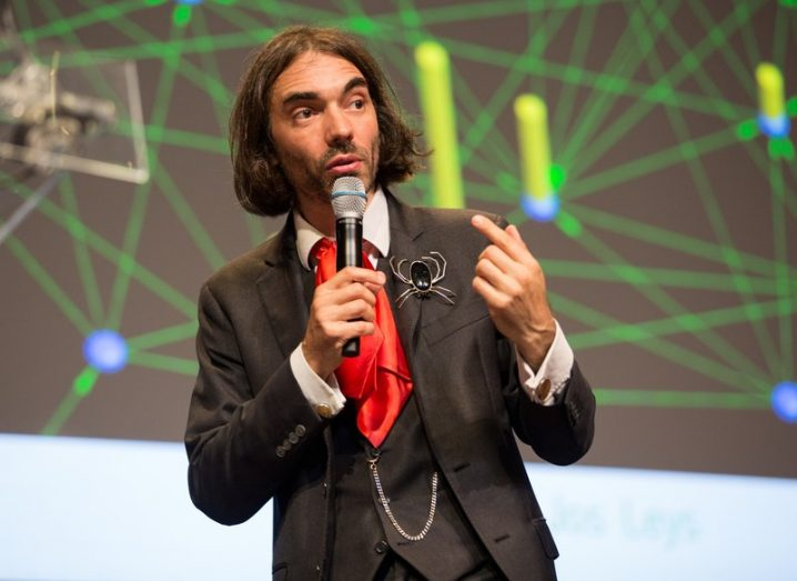 Cedric Villani giving a talk, wearing a three-piece suit, red cravat, and a brooch in the shape of a spider on the lapel.