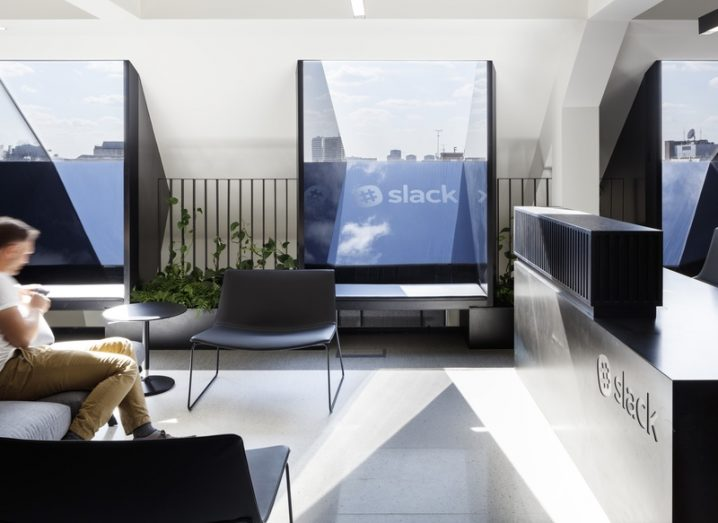 Some Slack team members sitting in its modern London office, featuring large glass panels and modern furniture.