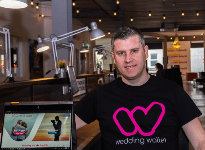 Man in black t-shirt with words Wedding Wallet emblazoned in pink. He is standing in an office setting beside a laptop with the Wedding Wallet website open.