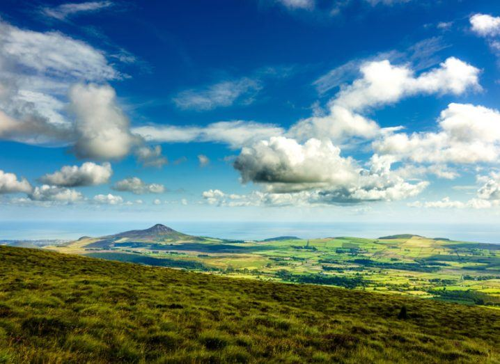 A view of the Wicklow Way in Ireland with green fields, mountains and sea under a canopy of clouds.