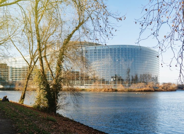 European Parliament buildings on the waterfront in Strasbourg, France on a sunny day with trees in the foreground.