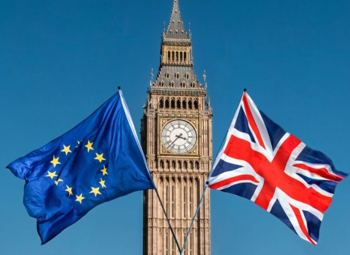 European Union and UK flags in front of Big Ben, with a blue sky in the background.
