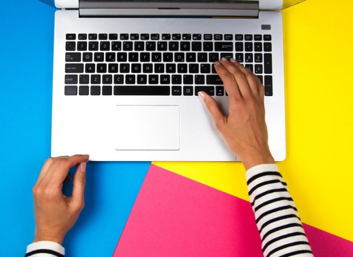 Top-down image of woman using a laptop on colourful background.