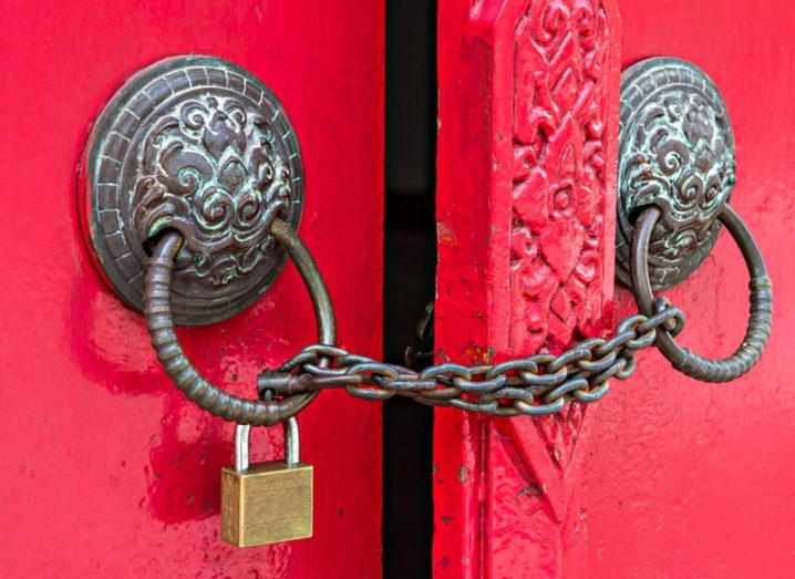 Red door with brass fittings locked using a chain and padlock, accessibility concept.
