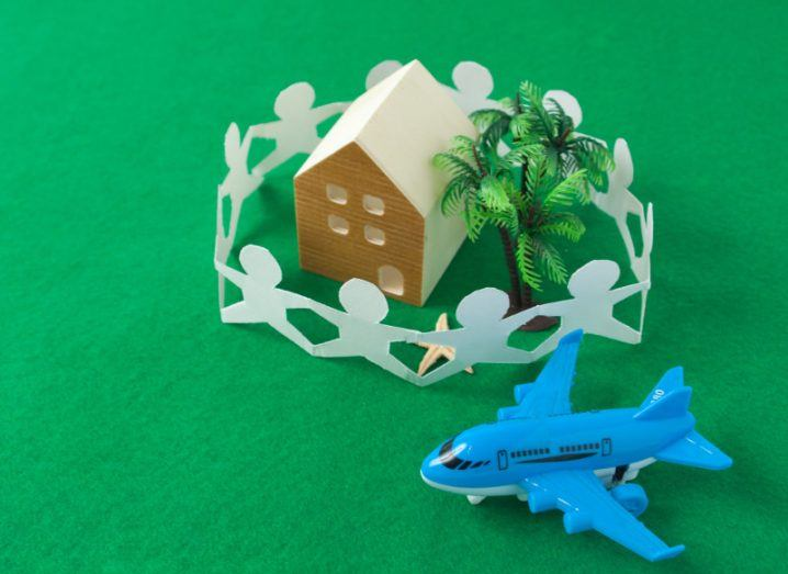 Mini toy house surrounded by paper cutouts of people beside a blue toy aeroplane on a model green field.
