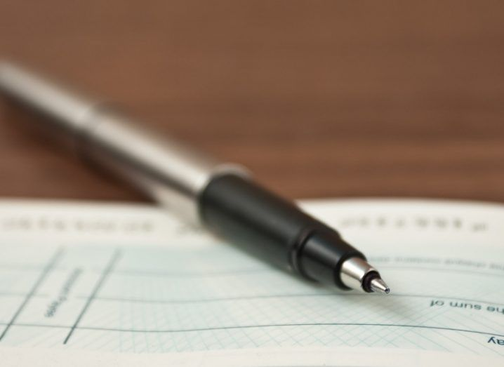 A picture of a silver pen lying across an open cheque book on a wooden table.