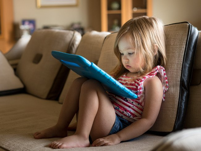 Young girl in stripey top sits on a beige couch looking at an iPad.