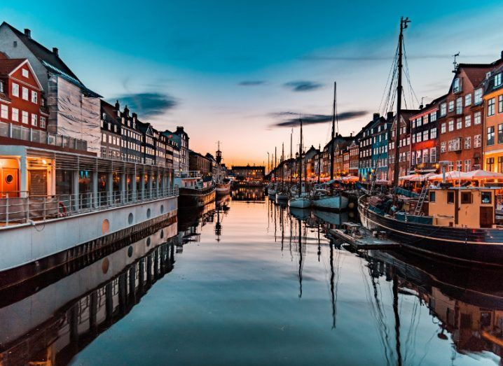View of Nyhavn in Copenhagen at golden hour, framed by picturesque colourful houses on either side with ships and reflective water in the centre.