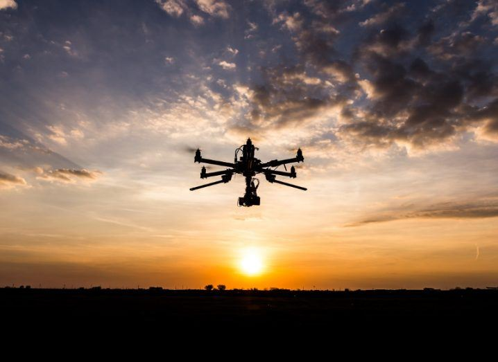 Picture of a drone flying in an evening sky above the setting sun over a dark landscape.
