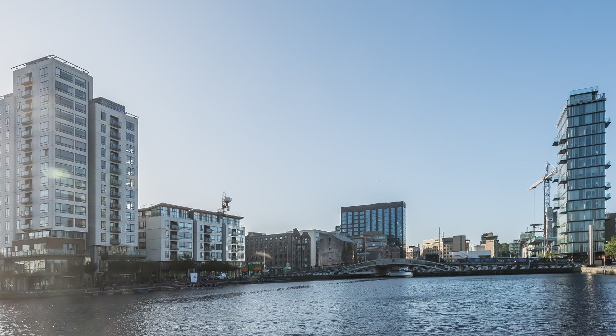 Panorama of Silicon Docks skyline in Dublin with a blue sky reflecting on water.