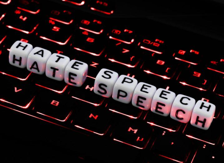 Picture of the words hate speech on a black keyboard backlit in red.