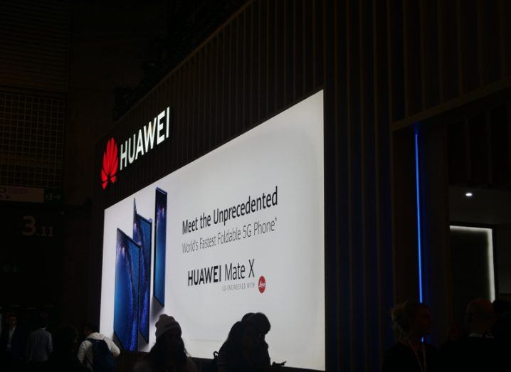 huawei logo above a sign for the new foldable Mate X smartphone at Mobile World Congress 2019.