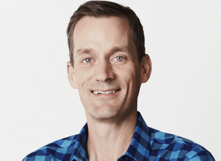 Man with short brown hair, green eyes and blue checkered shirt smiling at camera.