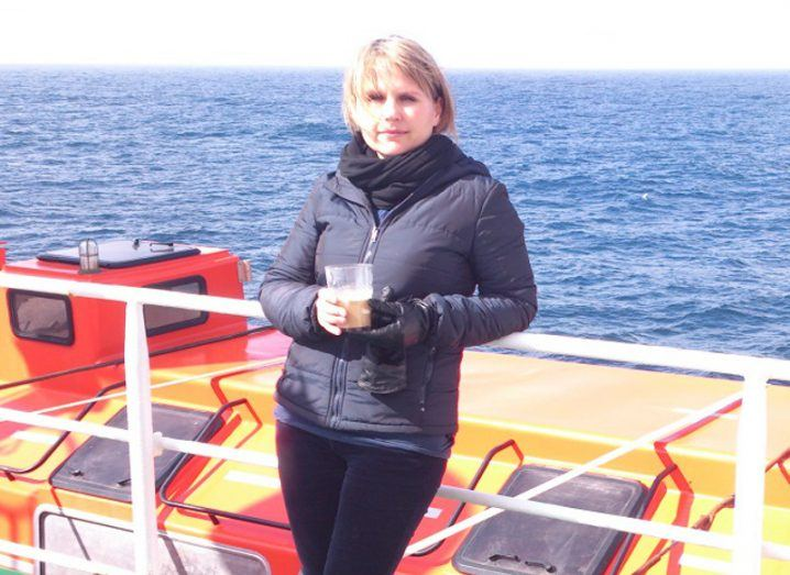 Jurgita Ovadnevaite in a navy puffy jacket leaning against a rail on board a ship at sea.