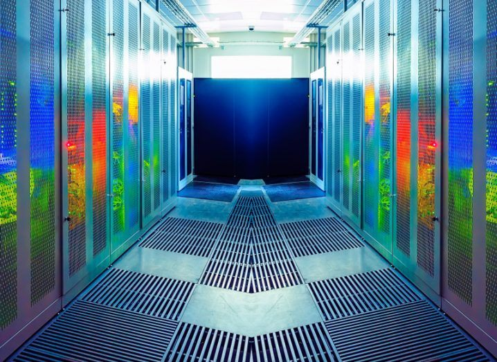 Image of the inside of a data centre with multi-coloured lights emanating from server racks.