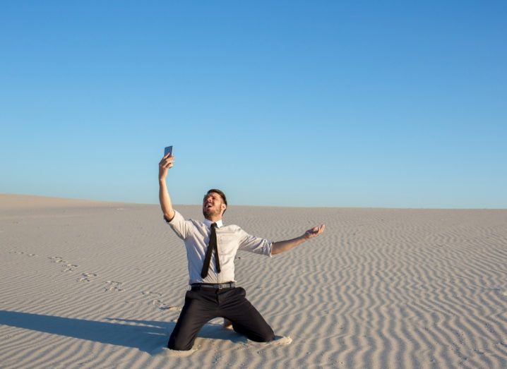 Man in white shirt, dark tie, kneeling and holding a phone up to the sky in a desert, hoping for a decent mobile signal.