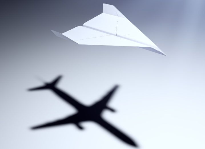 Paper aeroplane on grey background casting a shadow of a jetliner, symbolising testing design before the real thing.