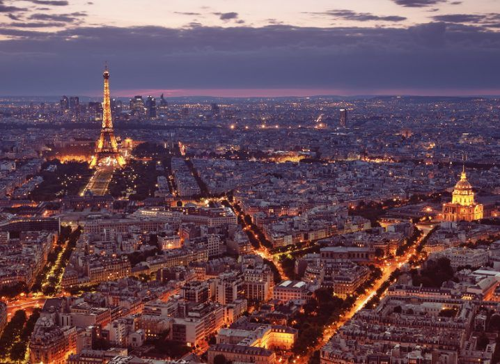 A view of the Paris skyline with the Eiffel Tower lit up under a purple clouded sky.