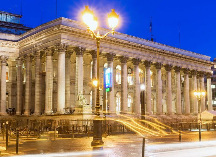 A picture of lights streaming by and into the Paris Bourse, or stock exchange, under a blue night sky.