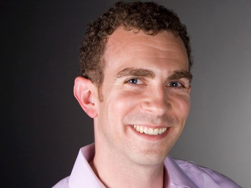 Smiling man with short curly hair in lilac shirt.