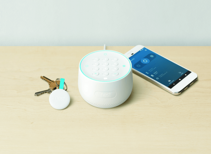 A set of house keys and a smartphone on a table. In the centre, a Nest Guard hub is placed. It is a round, white object with a keypad.