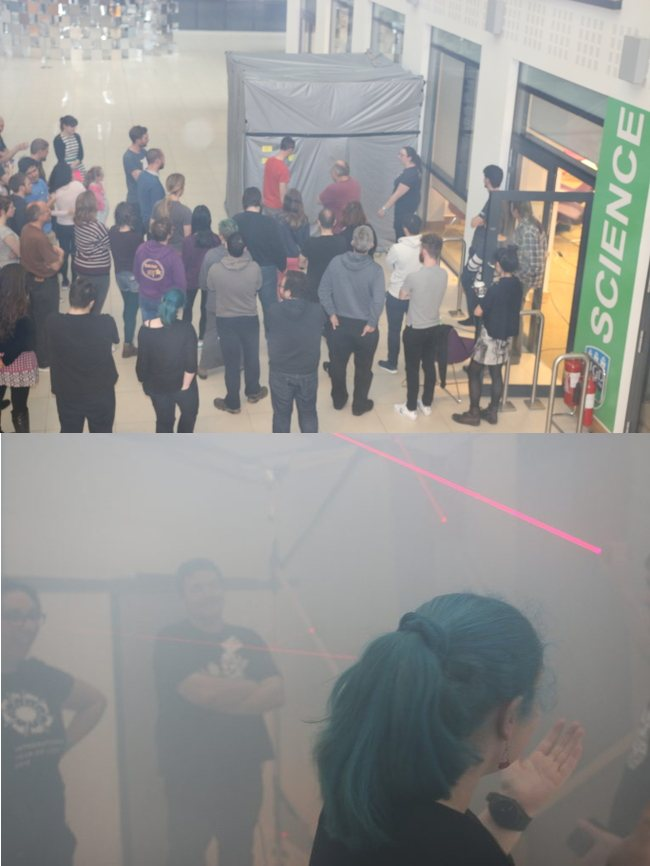 Two stacked images: on top, a crowd gathers around a tall grey cube structure; on the bottom, three people stand in the smoke-filled cube trying to navigate around red lasers.