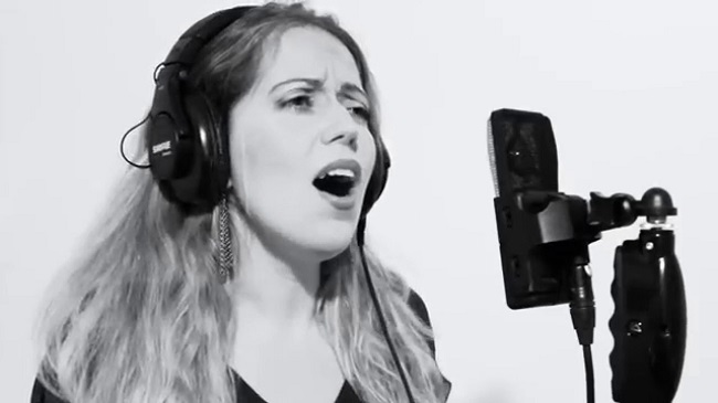Black and white image of Maya Ackerman singing into a microphone wearing headphones.