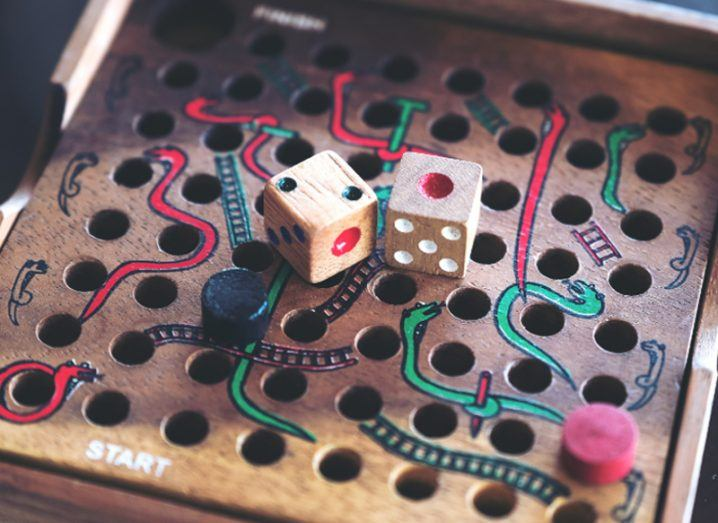 Close-up image of a wooden Snakes and Ladders game with dice, symbolising entrepreneurs taking a risk.