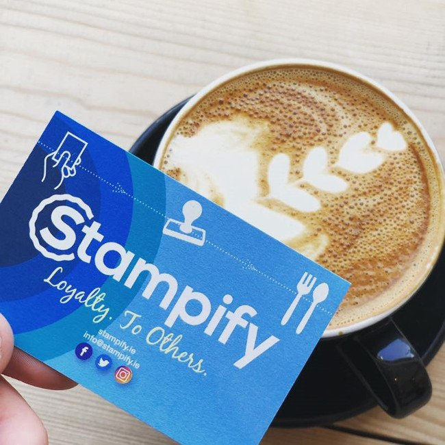 Image of a blue loyalty card with word Stampify on it beside a cup of coffee.