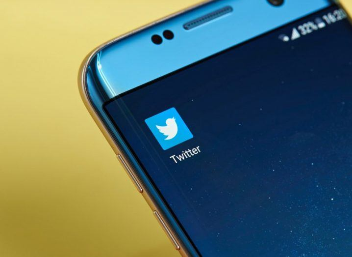 Twitter application icon on a blue smartphone screen against mustard yellow background.