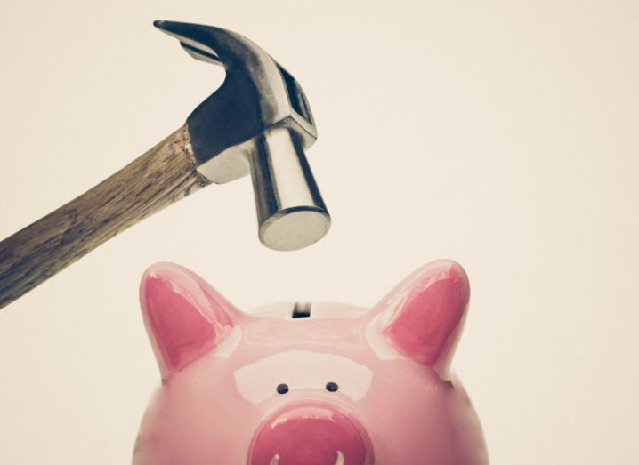 Picture of a hammer about to be taken to a ceramic pink piggy bank.