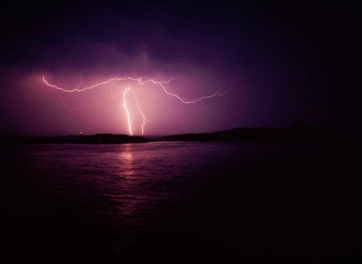 A lightning storm takes place over Dublin Bay in Ireland, casting the sky in a purple hue.