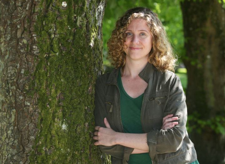 A casually dressed woman with curly hair smiles with her arms folded, leaning against a tree.