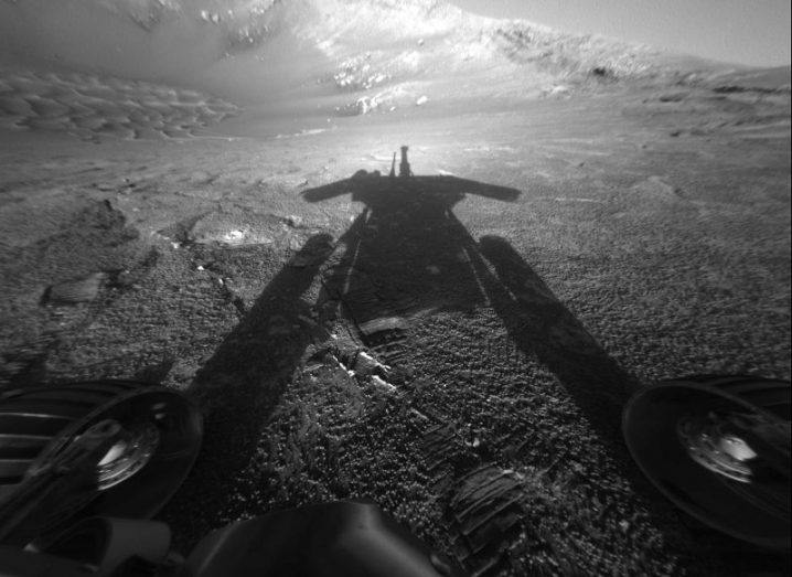black and white photo showing shadow of Mars Opportunity rover on surface of the planet.
