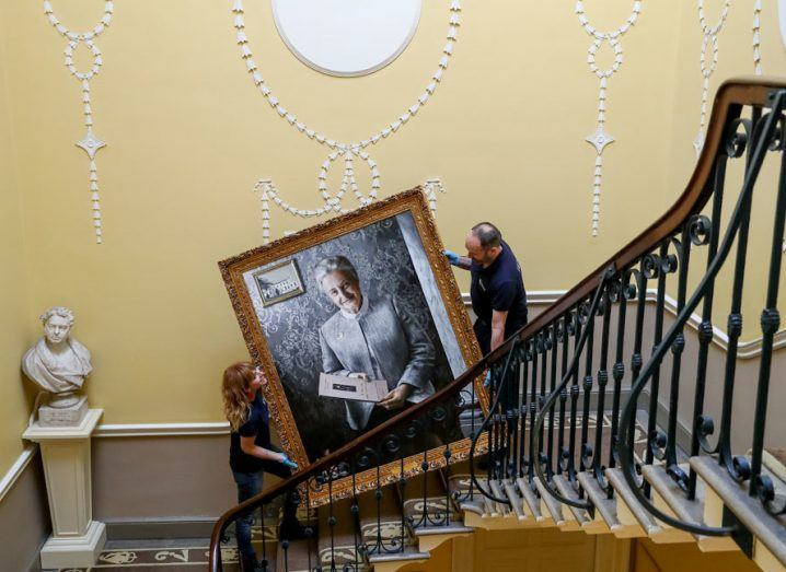A man and a woman carrying a large portrait of a woman up a grand staircase in the RCSI building.