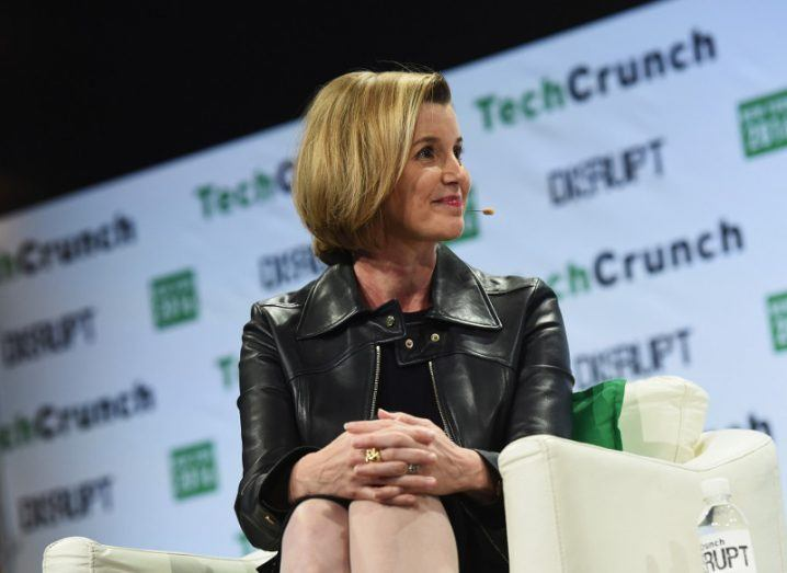 Woman with brown/blonde hair sits on a cream sofa on stage at a TechCrunch event in New York.
